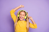 Portrait of funky crazy kid with ponytails listen music have break pause use headset sing song, dance on party wear trendy jumper isolated over violet color background