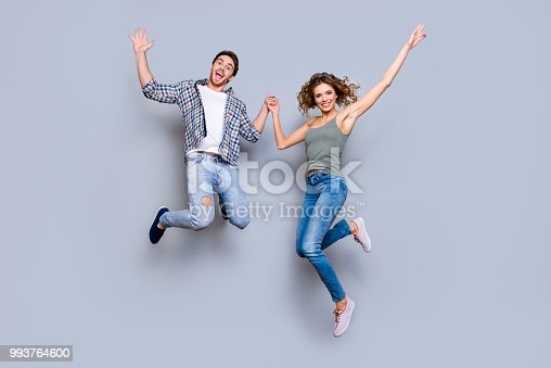 Portrait of funky foolish couple in jeans sneakers jumping in air holding hands up enjoying time together isolated on grey background. Move motion concept