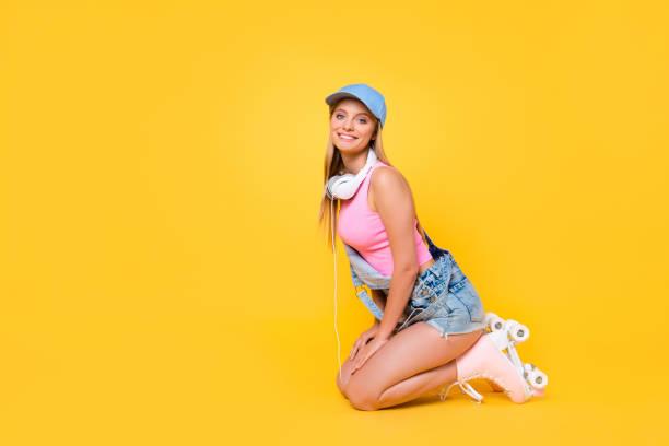 porträt von funky positive mädchen sitzen auf knien tragen rollschuhe denim outfit mit kopfhörer am hals strahlenden lächeln blick in die kamera auf gelbem hintergrund isoliert - jeans overall stock-fotos und bilder