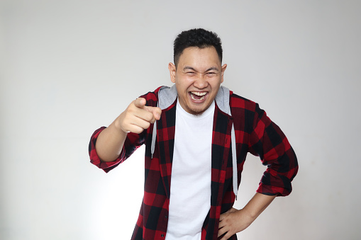 Portrait of funny Asian man laughing hard and pointing forward, bully expression against white background