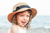 Portrait of funny child girl in hat on the beach with sea view.Vacation,summer concept