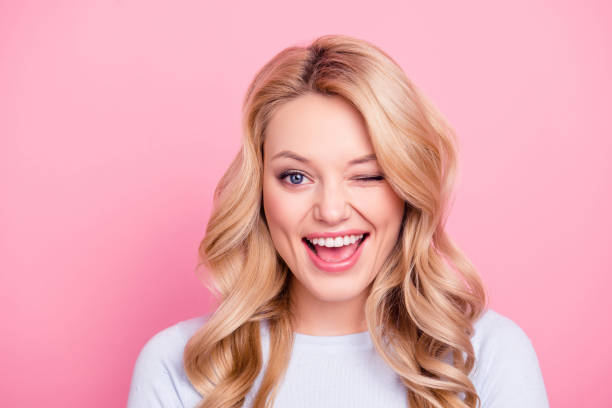 Portrait of funny foolish girl with modern hairdo winking with one eye open mouth, playing with lover isolated on pink background stock photo