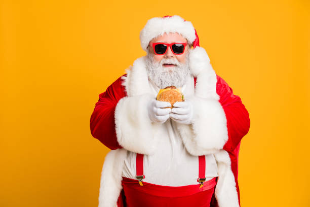 Portrait of funny funky fat santa claus dont care about health eat fast food big sandwich on x-mas tradition celebration wear style stylish suspenders isolated over shine color background stock photo