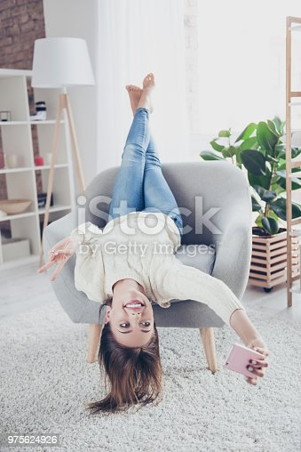 istock Portrait of funny funky girl lying head over heels shooting selfie on front camera using smart phone gesturing v-sign having video-call enjoying freetime in crazy mood 975624926