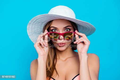 Portrait of funny impressed girl with amazed reaction wide open eyes looking out glasses holding eyelets isolated over blue background, summer sales