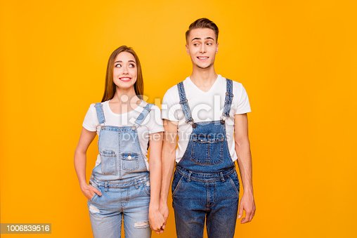 Portrait of funny lovely cute couple holding hands and looking at each other standing straight over yellow background, isolated