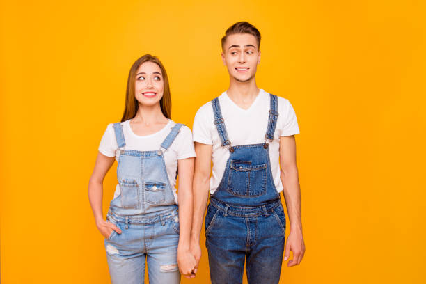Portrait of funny lovely cute couple holding hands and looking at each other standing straight over yellow background, isolated Portrait of funny lovely cute couple holding hands and looking at each other standing straight over yellow background, isolated bib overalls stock pictures, royalty-free photos & images