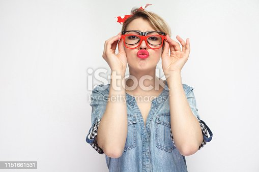 Portrait of funny young girl in casual blue denim shirt with makeup, red headband standing, trying many eyeglasses frames and sending air kiss to you. indoor studio shot, isolated on white background