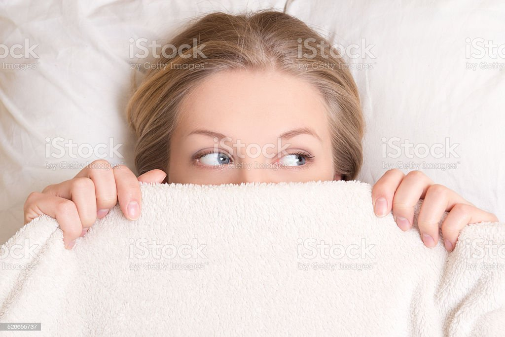 portrait of funny young woman lying in bed under blanket stock photo