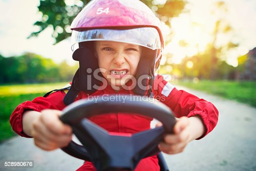 1035136022istockphoto Portrait of furious little boy riding a fast go-kart. 528980676