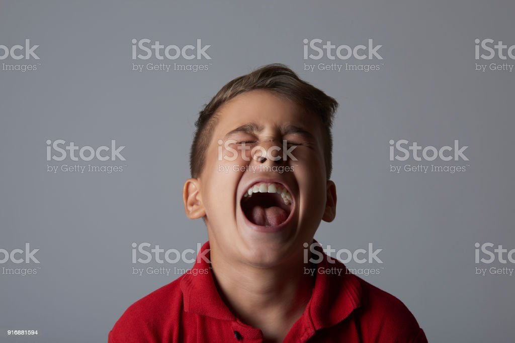 portrait of furious little boy screaming in pain over a gray