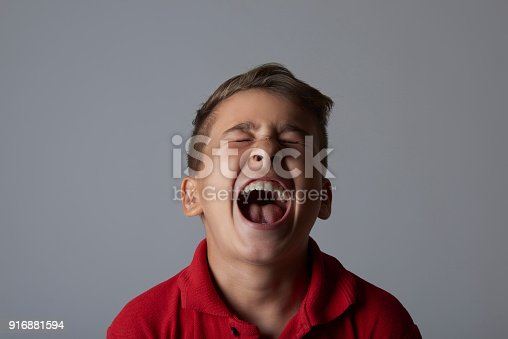 istock Portrait of furious little boy screaming in pain over a gray background 916881594