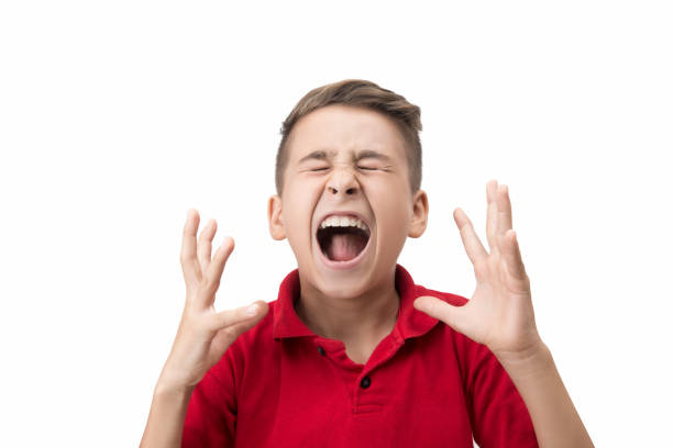 Portrait of furious little boy screaming in pain over white background stock photo