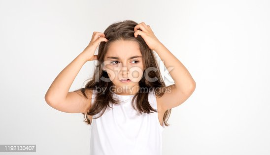 istock Portrait of furious little girl screaming. Angry little girl holding her hair with negative facial expression. sideways looking 1192130407