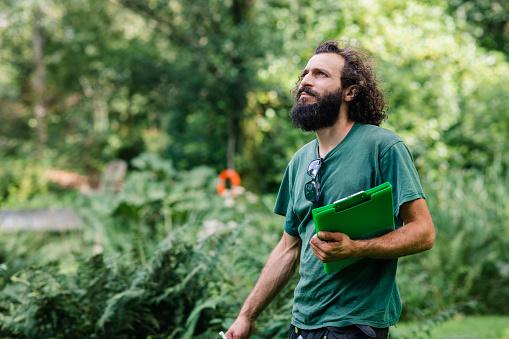 Portrait of gardener with clipboard looking up