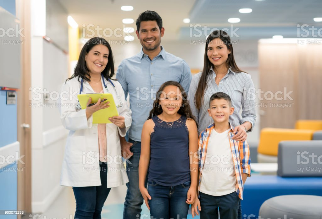 Portrait of general practitioner and a beautiful couple with two kids all looking at camera smiling stock photo