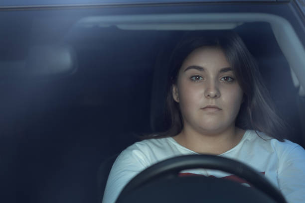 Portrait of girl driving car by night stock photo