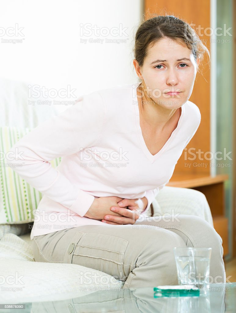 Portrait of girl folding up with belly pain indoor stock photo