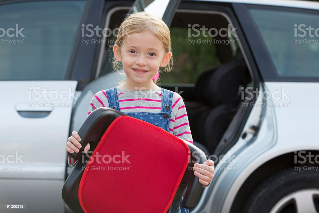 Portrait Of Girl Holding Booster Seat Standing Next To Car stock photo