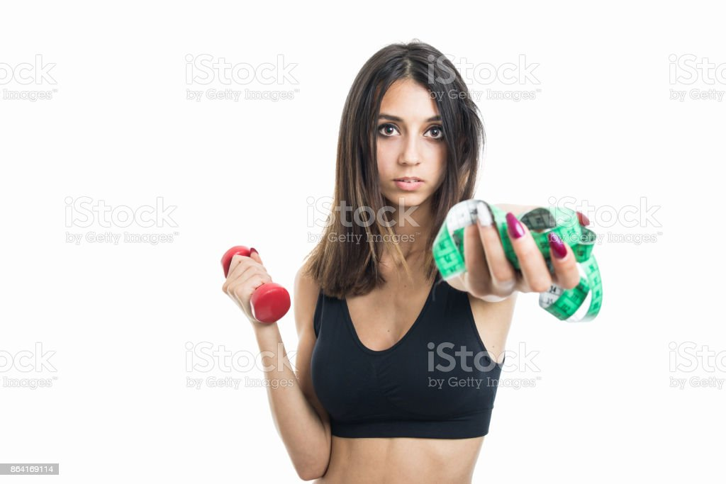 Portrait of girl holding measuring tape and dumbbell royalty-free stock photo