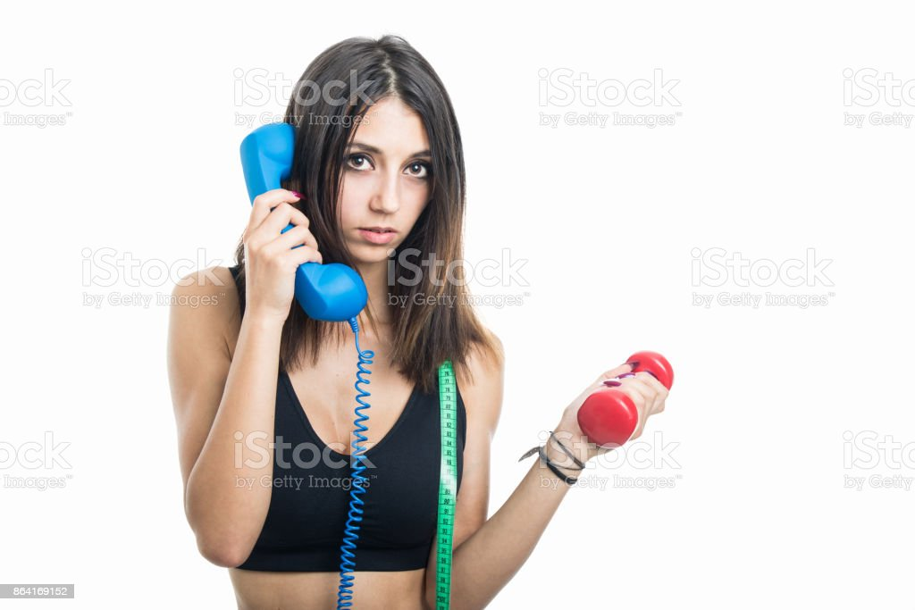 Portrait of girl holding phone receiver and dumbbell royalty-free stock photo