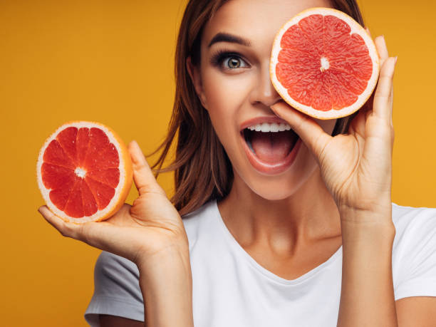 Portrait of girl holding red grapefruit stock photo