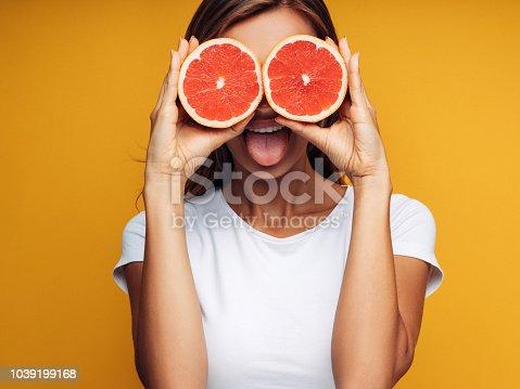 Portrait of girl holding red grapefruit