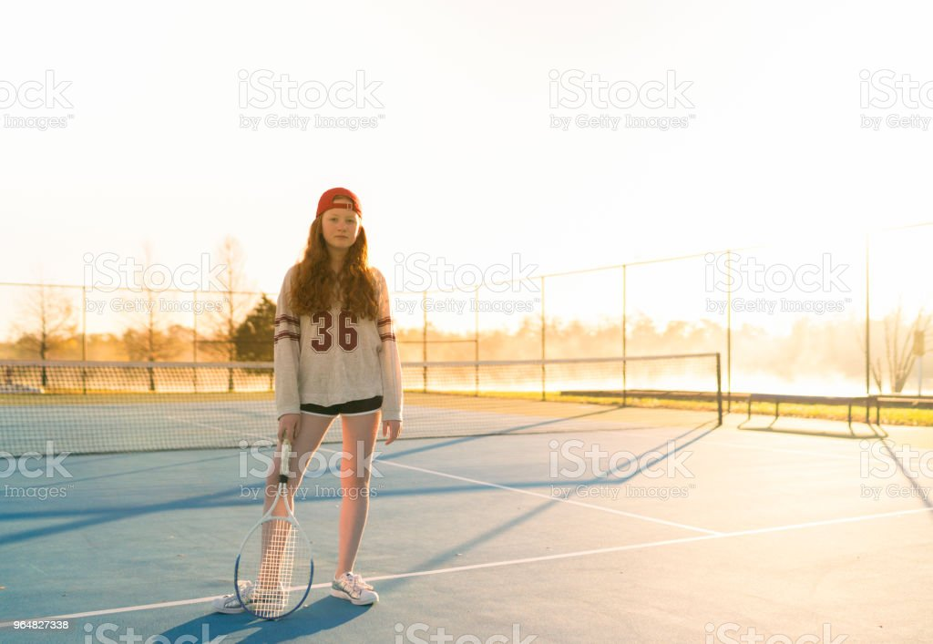 Portrait of girl holding tennis racket at court royalty-free stock photo