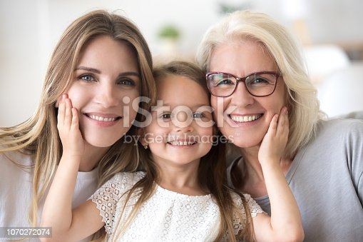 istock Portrait of girl hugging mom and grandmother making family picture 1070272074