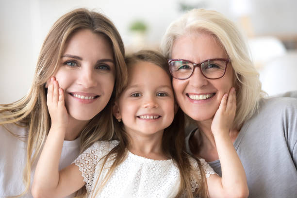 portrait of girl hugging mom and grandmother making family picture - granddaughter and grandmother stock photos and pictures