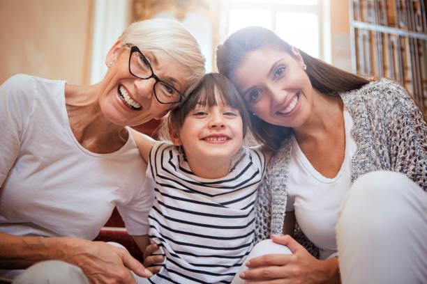 Porträt von Mädchen umarmen Mama und Großmutter lächelnd – Foto