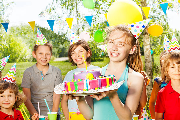 Portrait of girl in party hat holding B-day cake Laughing young girl in party hat holding birthday cake, standing among her friends at the outdoor party group of friends giving gifts to the birthday girl stock pictures, royalty-free photos & images