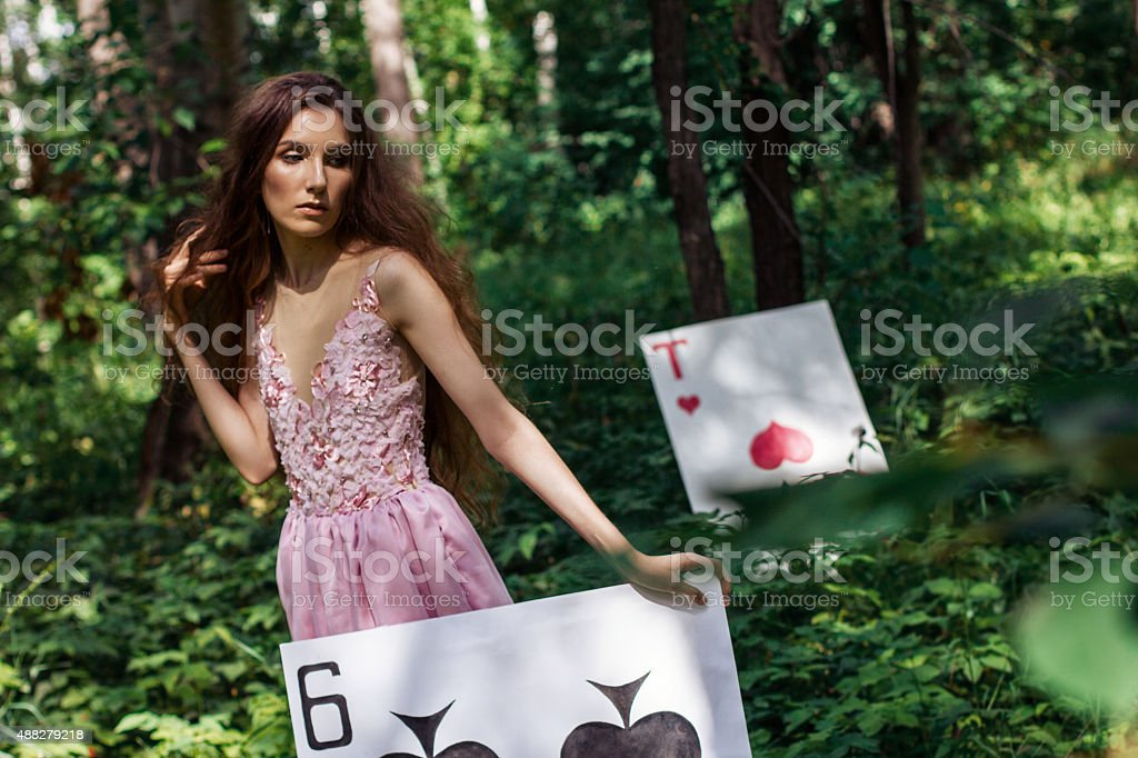 portrait of  girl in pink dress as Alice in Wonderland stock photo