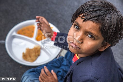 941788480 istock photo Portrait of Girl kid having mid-day meal in Indian school. 941788480