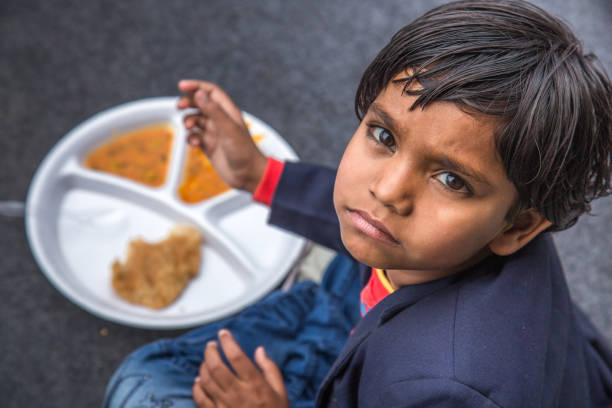 Portrait of Girl kid having mid-day meal in Indian school. Indian school children eat their free midday meal at a government school in Haryana hungry stock pictures, royalty-free photos & images