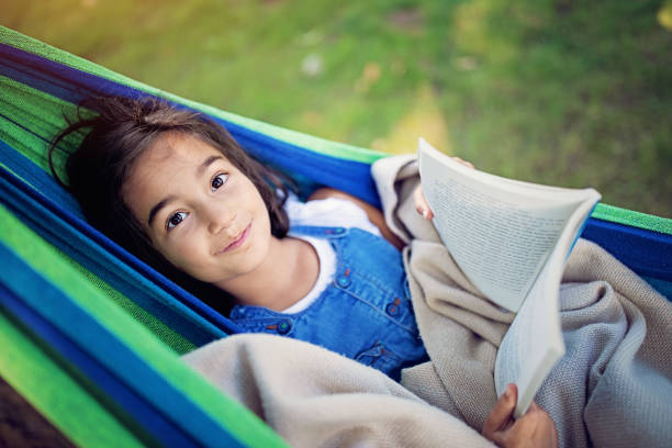 Portrait of girl lying in the hammock and reading book stock photo
