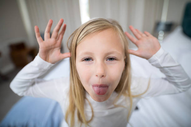 Portrait of girl making facial expression in bedroom stock photo