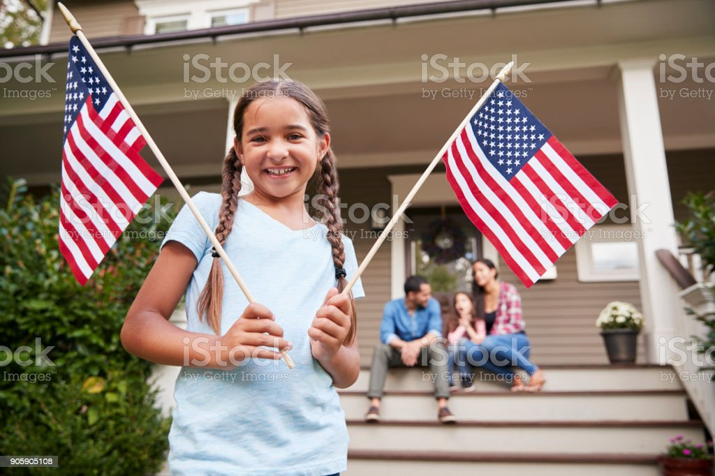 Portrait Of Girl Outside Family Home Holding American Flags stock photo