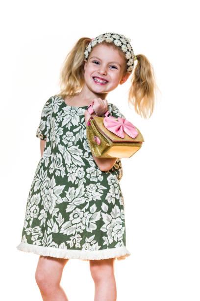 porträt eines mädchens lustige grimassen, eine handtasche tragen - kinderhandtaschen stock-fotos und bilder