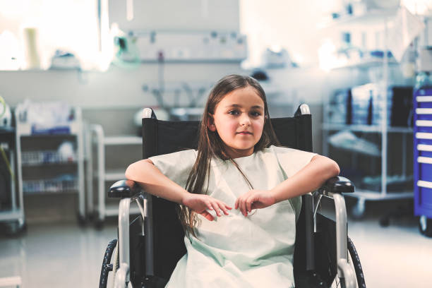 Portrait of girl sitting on wheelchair in hospital Portrait of smiling patient sitting on wheelchair. Girl is wearing hospital gown. She is in hospital. paralysis stock pictures, royalty-free photos & images