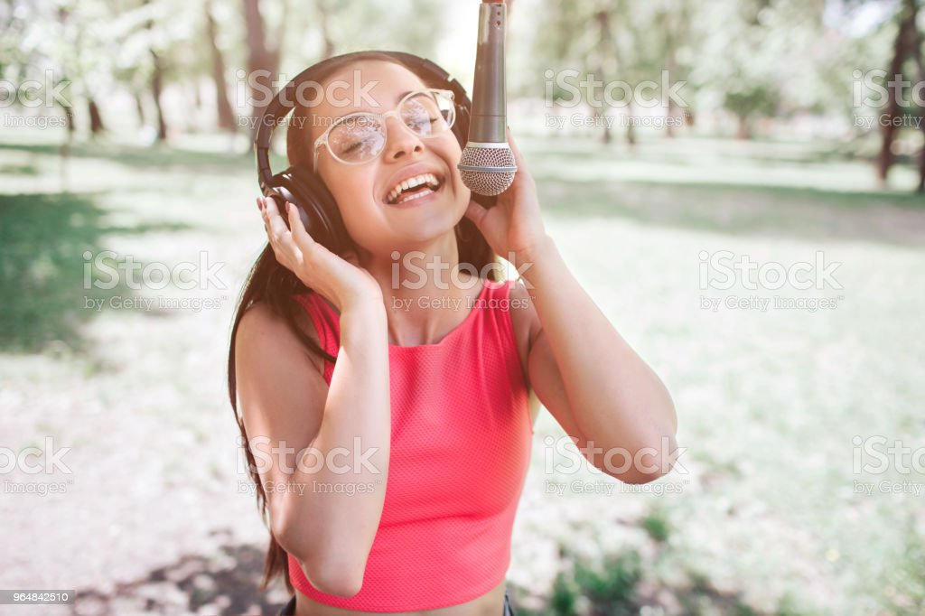 Portrait of girl standing outside and singing to the mic. She is listening to music at the same time while she is singing. Young woman is enjoying the moment royalty-free stock photo