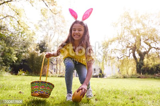 Portrait Of Girl Wearing Bunny Ears Finding Chocolate Egg On Easter Egg Hunt In Garden