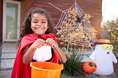 istock Portrait Of Girl Wearing Fancy Dress Outside House Collecting Candy For Trick Or Treat 1271509012