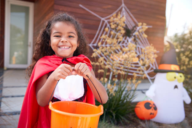 Portrait Of Girl Wearing Fancy Dress Outside House Collecting Candy For Trick Or Treat stock photo