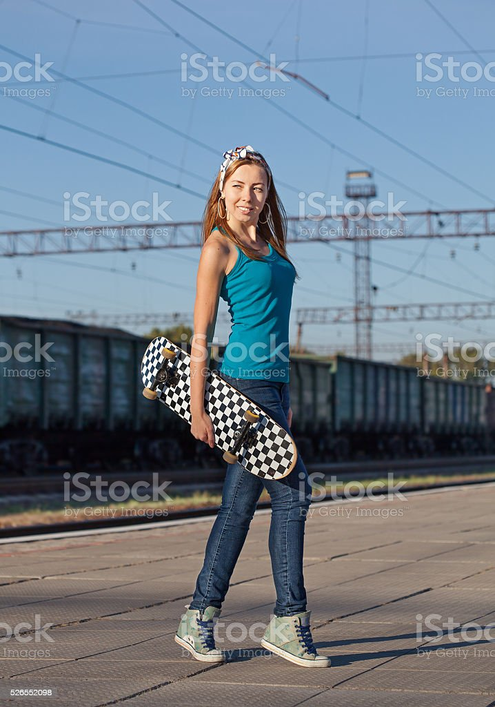 Portrait of  girl with a skateboard. Woman on railway station stock photo