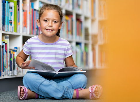 Portrait of cute girl sitting in library. Full length of student is wearing casuals. She is reading book in school.