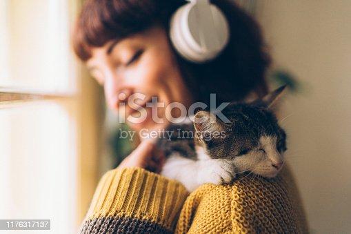 Woman hugging cat and enjoying the music