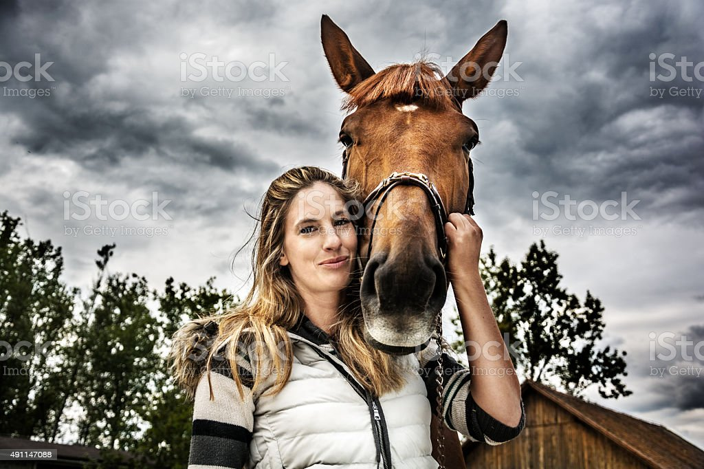 Portrait of girl with her horse on stormy day stock photo