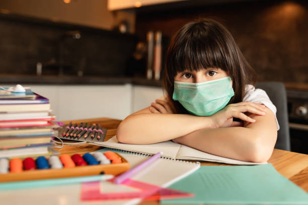 Portrait of girl with protective mask on face at home. Online learning concept stock photo