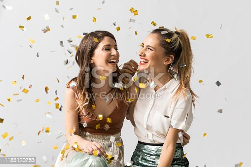Portrait of two beautiful laughing young women feeling happy together celebrating under confetti.
